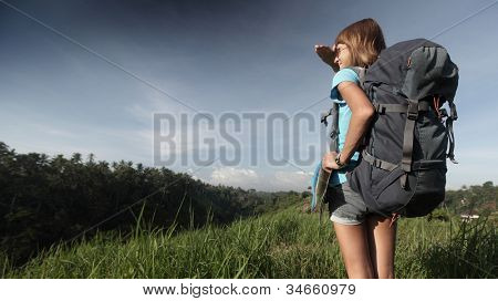 Young backpacker standing on a green meadow and looking to somewhere
