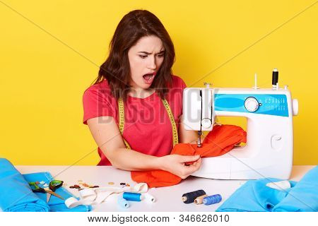Picture Of Shocked Desperate Young Inexperienced Seamstress Working With Red Fabric, Having Troubles