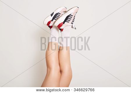 Hoprizontal Shot Of Cool Leather Sneakers, Female Legs Wearing White Socks And Snickers, Model Legs