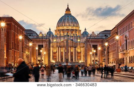 Vatican City Holy( See). Rome, Italy. Dome of St. Peters Basil cathedral at Saint Peters Square. Evening sunset, golden hour with evening sky and street lamps.