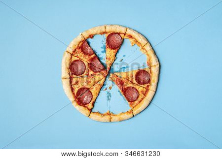 Pizza Pepperoni Slices And Leftover Crust On Blue Background. Above View Of Sliced Pizza Salami With