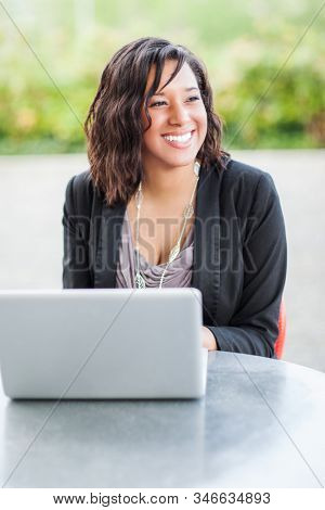 A shot of a happy African American businesswoman working on her laptop