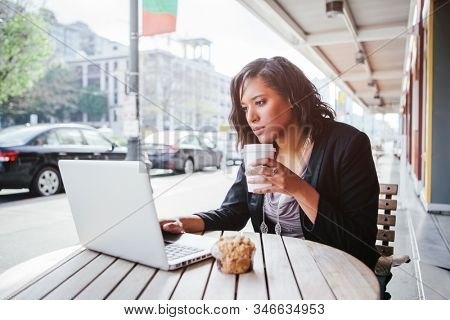 A shot of an African American businesswoman working on her laptop at an outdoor cafe