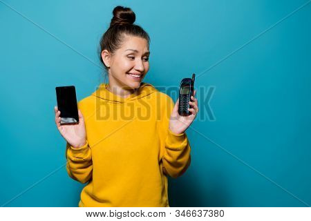 Girl Smiles At An Old Cell Phone, Which She Holds In Her Hand, Holding A Modern Smartphone In Her Se