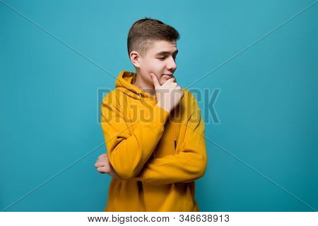 Young Man In A Yellow Sweatshirt On A Blue Background, Looking Thoughtfully, Looks Towards An Imagin