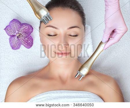 The Cosmetologist Does Rf-lifting Of The Face Skin Of A Beautiful Woman In A Beauty Salon. Rf Liftin