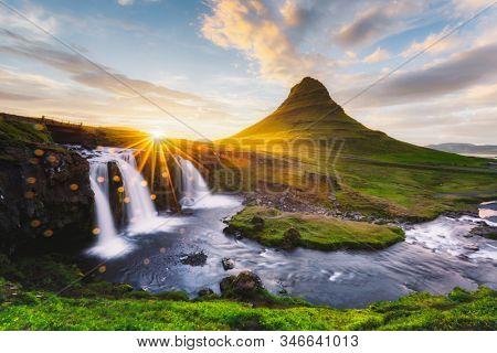 Morning landscape with rising sun on Kirkjufellsfoss waterfall and Kirkjufell mountain, Iceland, Europe. Landscape photography
