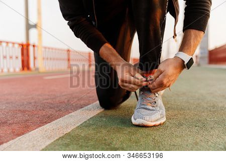 Close up of a young fit sportsman working out on a bridge, tying shoelace