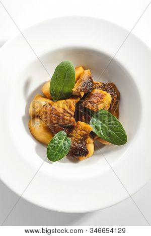 Roasted boletus or porcini mushrooms with baked potatoes and fresh spinach greens on white restaurant plate isolated. Fried delicious ceps, porcino or penny bun healthy dining topview