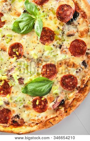 Pizza with marbled beef, ham, salami and chorrizo on metal tray in italy pizzeria isolated. Traditional italian meet pizza with cooked veal, mozzarella and basil, delicious fast food topview