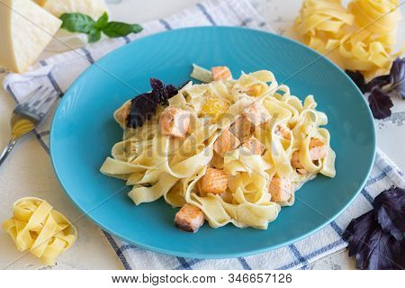 Carbonara Pasta With Salmon In A Creamy Sauce On A Blue Plate.