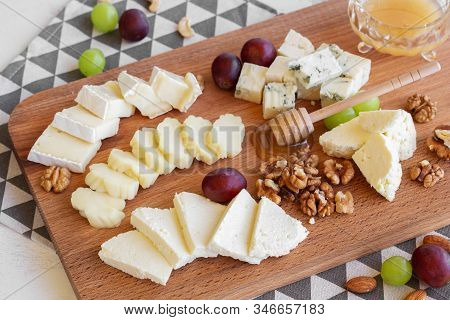 Assorted Cheeses On A Board With Nuts, Honey And Grapes.