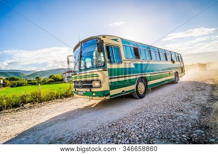 Berat, Albania - July 31, 2014. Old Green Bus On Dirt Road In Sunset