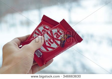 Kit Kat Chocolate Bar In Male Hand On Snowy Background. Kit Kat Created By Rowntrees Of York In Unit