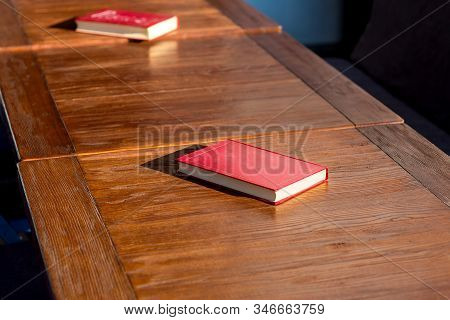 Untitled Red Hardcover Book On A Wooden Brown Table Lit By The Sunlight Of A Empty Street Cafe, Nobo