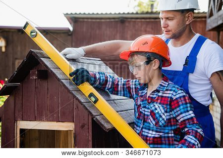 The Boy Holds The Building Level, Checking The Accuracy Of The Dog House Roof.
