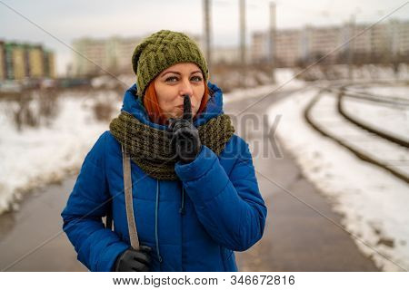 Beautiful Young Red-haired Woman In Casual Clothes Smiles And Does Gesture Of Silence With Index Fin