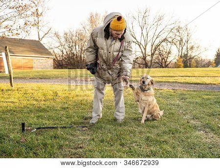 November 25, 2019, Berks County, Pennsylvania, Older Man Asks His Dog To Shake Hands.