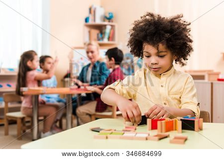 Selective Focus Of African American Kid Playing Educational Game With Teacher And Children At Backgr