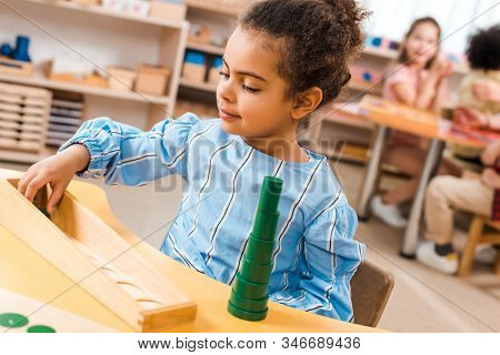 Selective Focus Of Child Playing Educational Game With Kids At Background In Montessori Class