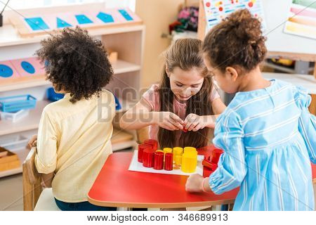 Children Playing Colorful Educational Game At Desk In Montessori School