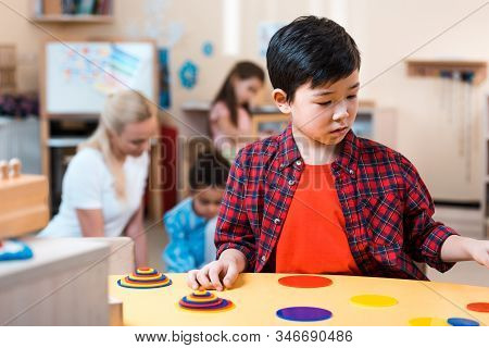 Selective Focus Of Asian Kid Folding Game And Teacher With Children At Background In Montessori Scho