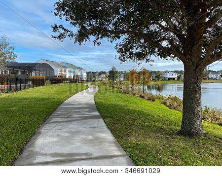 Orlando, Fl/usa-1/23/20: A Curved Sidewalk Near A Lake That Is A Walking Path Behind Homes In Laurea