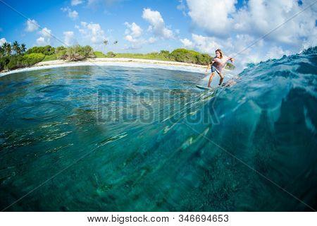 HURAA / MALDIVES - MARCH 22, 2019: Young surfer rides the ocean wave at the Honkeys surf spot in Maldives