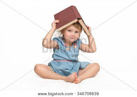 Cute Little Child In Blue Dress Reading A Book