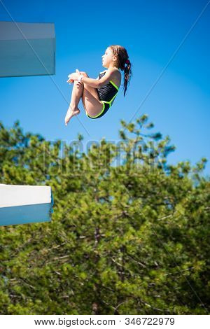 Little Caucasian Female 8 Years Old Girl Diver Jumping In Crouching Position For Make A Back Dive Fr