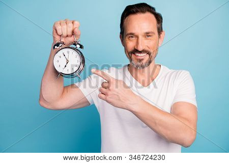 Close-up Portrait Of Nice Attractive Cheerful Cheery Guy Holding In Hand Showing Clock Healthy Sleep