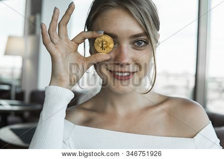 Close Up Fun Emotional Young Female Is Holding Bitcoin In Front Eye. Online Virtual Future Currency