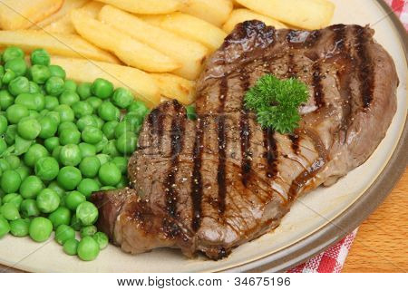 Chargrilled sirloin steak with chunky chips and peas.