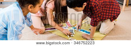 Panoramic Shot Of Kids Playing Colorful Game On Floor In Montessori School
