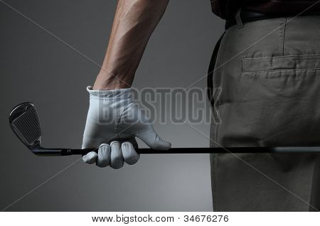 Closeup of a male golfer holding a six iron behind his body. Man has a Golf Glove on his hand. Horizontal format over a light to dark gray background.