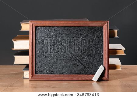 Education Background. School Blackboard With Copy Space, Chalk And Stack Of Books On The Desk.