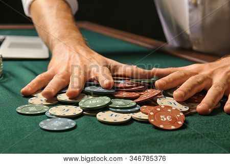 A Man Collects Chips On A Table In A Casino