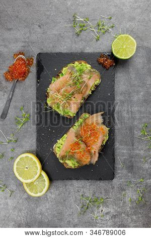 Sandwiches With Avocado, Red Fish, Watercress And Red Caviar On A Black Stone Stand With Lemons And