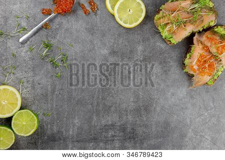 Spoon With Red Caviar, Watercress, Lemons And Bread With Avocado And Red Fish On A Dark Background.