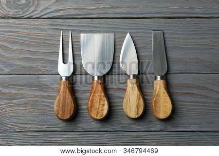 Cheese Knives On Wooden Background, Top View And Space For Text