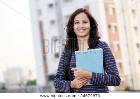 Smiling Young Female Student Holding Books