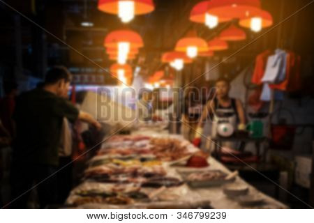 Abstract, Blurred Concept Image Of People   Buying Fish On Food Market In Hong Kong