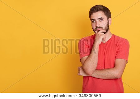 Picture Of Young Cool Caucasian Man Confused, Feels Doubtful And Unsure, Keeping Hands Ubder Chin, L