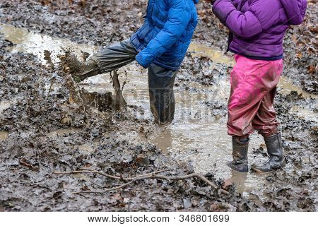Young Children Playing In A Muddy Puddle