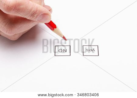 The Hand Holding The Red Pencil Makes A Choice By Putting A Tick In The Voting Form