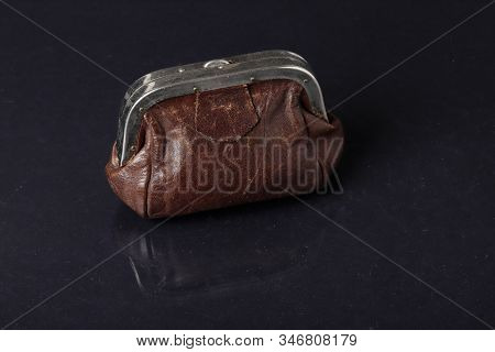 A Closed Brown Used Leather Purse Reflected On Dark Background.