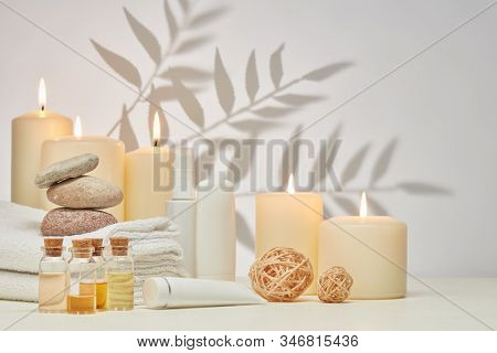 Spa still life with creams, essential oils, burning candles, stones and towels on light background with shadow from plant. Healthy lifestyle, body care, Spa treatment.