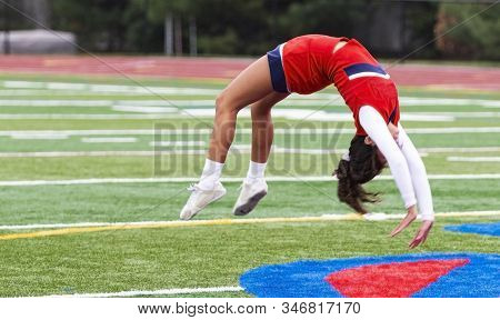 High School Cheeleader Is Upside Down While Doing Back Flips On A Green Turf Field.