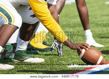 A High School Football Center Is Lined Up And Ready To Snap The Ball To Start The Play.