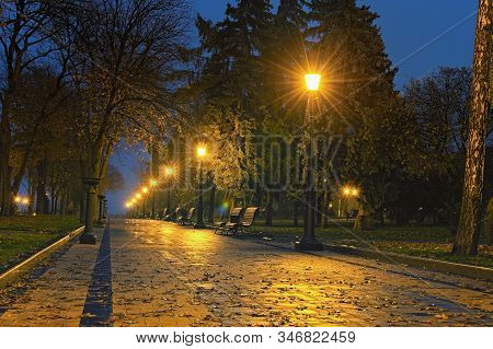 Romantic Landscape View Of Saint Volodymyr Hill At Night. A Deserted Straight Alley With Benches And
